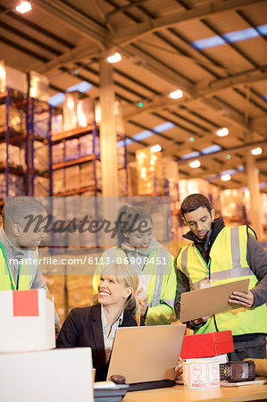 Businesswoman and workers talking in warehouse Stock Photo - Premium Royalty-Free, Image code: 6113-06908451