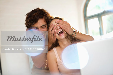 Man covering girlfriend's eyes indoors Stock Photo - Premium Royalty-Free, Image code: 6113-06908495