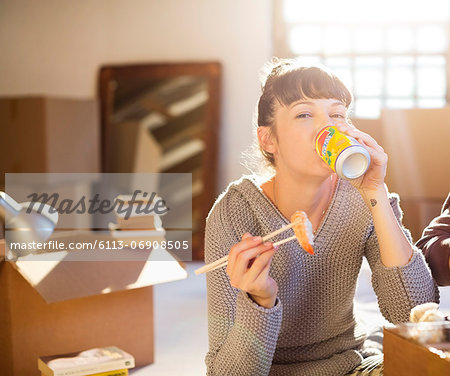 Woman drinking soda and eating sushi in new home Stock Photo - Premium Royalty-Free, Image code: 6113-06908505