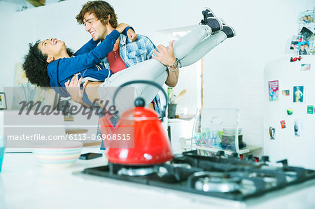 Couple playing together in kitchen Stock Photo - Premium Royalty-Free, Image code: 6113-06908515