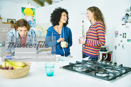 Friends relaxing together in kitchen Stock Photo - Premium Royalty-Free, Image code: 6113-06908524