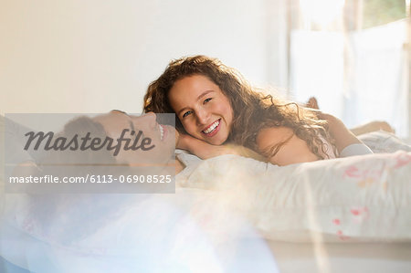 Couple relaxing together in bed Stock Photo - Premium Royalty-Free, Image code: 6113-06908525