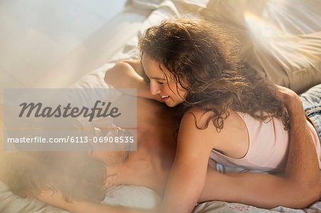 Couple relaxing together in bed Stock Photo - Premium Royalty-Free, Image code: 6113-06908535