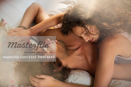 Couple relaxing together in bed Stock Photo - Premium Royalty-Free, Image code: 6113-06908543