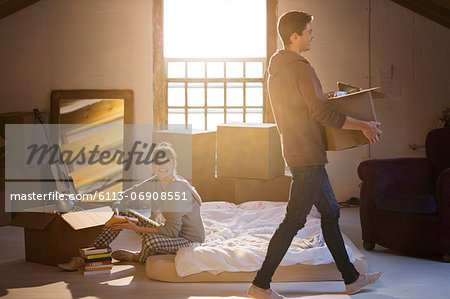 Couple unpacking boxes in attic Stock Photo - Premium Royalty-Free, Image code: 6113-06908551