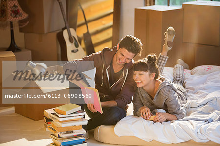 Couple unpacking books in new home Stock Photo - Premium Royalty-Free, Image code: 6113-06908560
