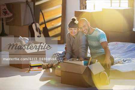 Couple unpacking boxes in attic Stock Photo - Premium Royalty-Free, Image code: 6113-06908564