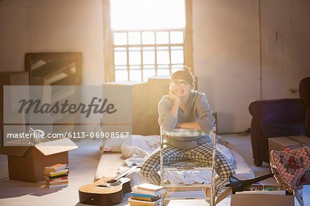 Woman unpacking boxes in attic Stock Photo - Premium Royalty-Free, Image code: 6113-06908567