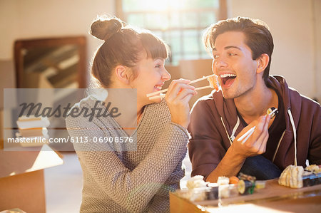 Couple eating sushi together in new home Stock Photo - Premium Royalty-Free, Image code: 6113-06908576