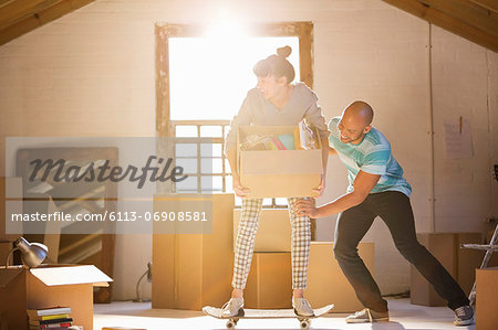 Couple unpacking boxes in new home Stock Photo - Premium Royalty-Free, Image code: 6113-06908581