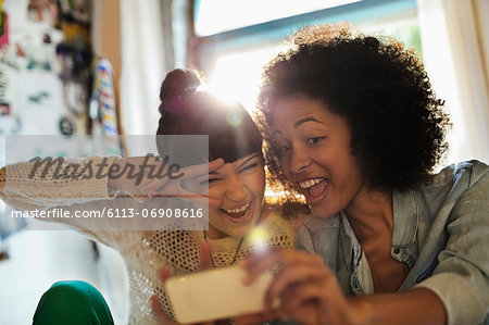 Women taking picture together Stock Photo - Premium Royalty-Free, Image code: 6113-06908616