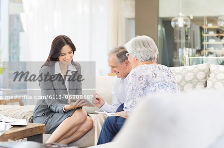 Financial advisor using tablet computer with clients Stock Photo - Premium Royalty-Free, Image code: 6113-06908687
