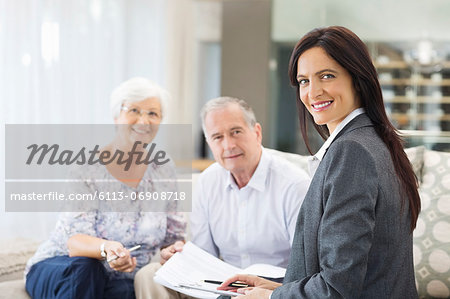 Financial advisor talking to couple on sofa Stock Photo - Premium Royalty-Free, Image code: 6113-06908718