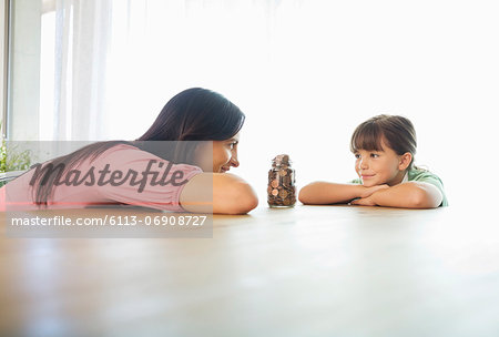 Mother and daughter with change jar Stock Photo - Premium Royalty-Free, Image code: 6113-06908727
