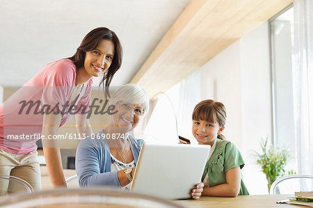 Three generations of women using laptop together Stock Photo - Premium Royalty-Free, Image code: 6113-06908747