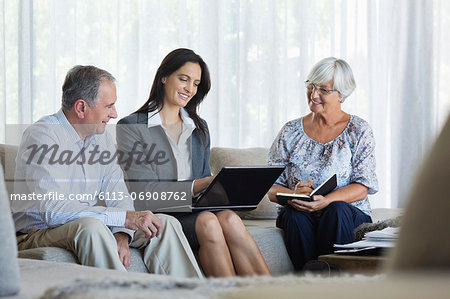Financial advisor talking to couple on sofa Stock Photo - Premium Royalty-Free, Image code: 6113-06908762