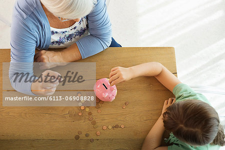 Older woman and granddaughter filling piggy bank Stock Photo - Premium Royalty-Free, Image code: 6113-06908828