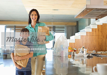 Mother and son holding groceries in kitchen Stock Photo - Premium Royalty-Free, Image code: 6113-06908833