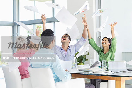 Business people tossing papers in air in meeting Stock Photo - Premium Royalty-Free, Image code: 6113-06908877