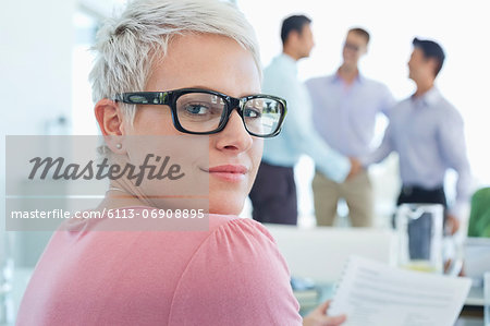 Businesswoman smiling in office Stock Photo - Premium Royalty-Free, Image code: 6113-06908895