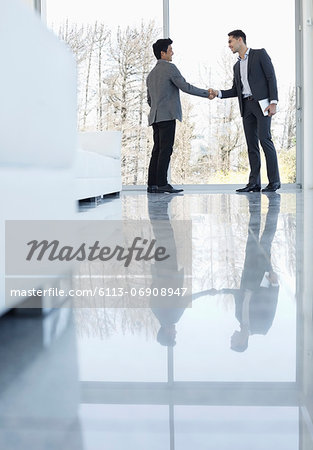 Businessmen shaking hands in office Stock Photo - Premium Royalty-Free, Image code: 6113-06908947