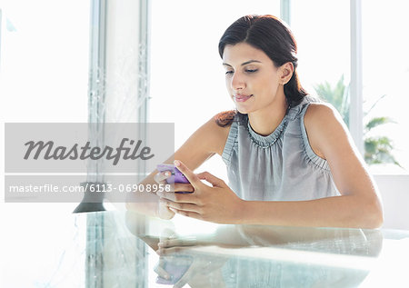 Businesswoman using cell phone at desk Stock Photo - Premium Royalty-Free, Image code: 6113-06908958
