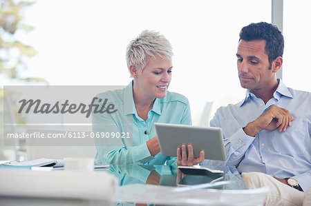 Business people using tablet computer on sofa Stock Photo - Premium Royalty-Free, Image code: 6113-06909021