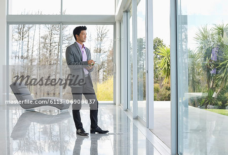 Businessman standing at office window Stock Photo - Premium Royalty-Free, Image code: 6113-06909037