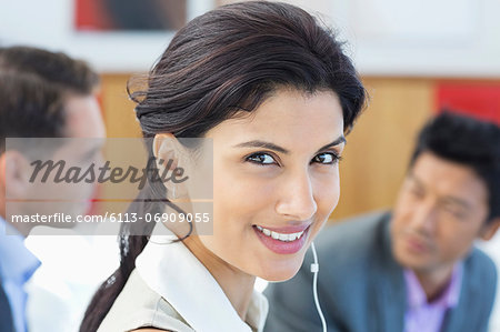 Businesswoman listening to headphones in office Stock Photo - Premium Royalty-Free, Image code: 6113-06909055
