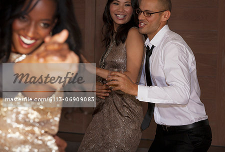 Friends dancing at party Stock Photo - Premium Royalty-Free, Image code: 6113-06909083