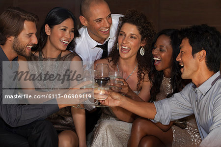 Friends toasting each other at party Stock Photo - Premium Royalty-Free, Image code: 6113-06909119