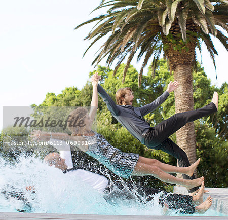 Friends jumping backwards into swimming pool Stock Photo - Premium Royalty-Free, Image code: 6113-06909147