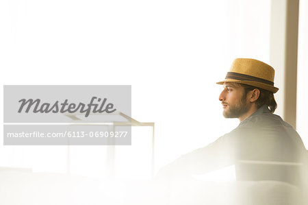 Man in straw hat looking out window