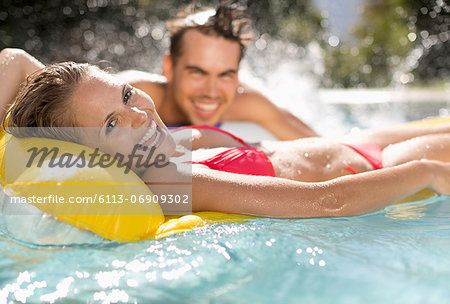 Couple relaxing in swimming pool Stock Photo - Premium Royalty-Free, Image code: 6113-06909302