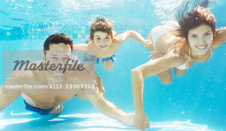 Family swimming in pool Stock Photo - Premium Royalty-Free, Image code: 6113-06909303