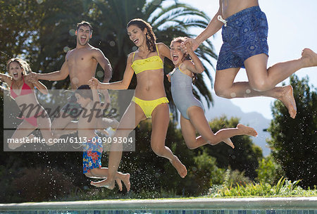 Family jumping into swimming pool Stock Photo - Premium Royalty-Free, Image code: 6113-06909304