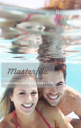 Couple smiling in swimming pool Stock Photo - Premium Royalty-Free, Image code: 6113-06909310