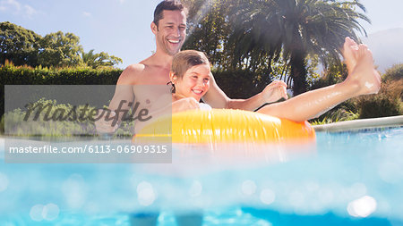 Father and son playing in swimming pool Stock Photo - Premium Royalty-Free, Image code: 6113-06909315