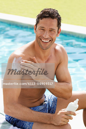 Man applying sunscreen by swimming pool Stock Photo - Premium Royalty-Free, Image code: 6113-06909317