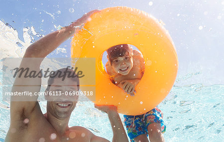 Father and son playing in swimming pool Stock Photo - Premium Royalty-Free, Image code: 6113-06909318