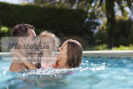 Family playing in swimming pool Stock Photo - Premium Royalty-Free, Image code: 6113-06909320