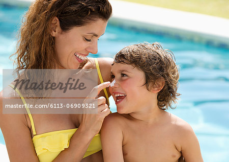 Mother applying sunscreen to son's face Stock Photo - Premium Royalty-Free, Image code: 6113-06909321