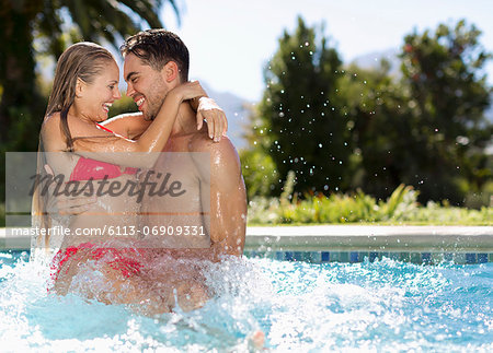 Couple playing in swimming pool Stock Photo - Premium Royalty-Free, Image code: 6113-06909331