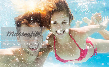 Couple swimming in pool Stock Photo - Premium Royalty-Free, Image code: 6113-06909333