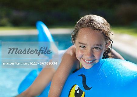 Girl riding inflatable toy in swimming pool Stock Photo - Premium Royalty-Free, Image code: 6113-06909334