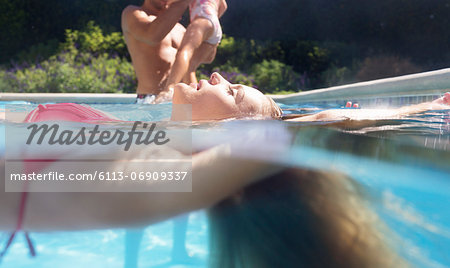 Woman floating in swimming pool Stock Photo - Premium Royalty-Free, Image code: 6113-06909337