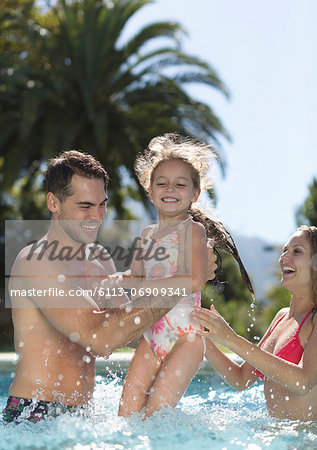 Family playing in swimming pool Stock Photo - Premium Royalty-Free, Image code: 6113-06909341
