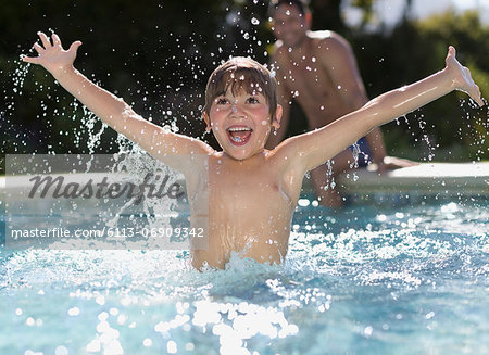 Boy playing in swimming pool Stock Photo - Premium Royalty-Free, Image code: 6113-06909342