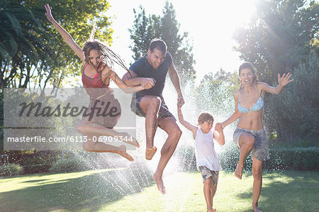 Family jumping in sprinkler Stock Photo - Premium Royalty-Free, Image code: 6113-06909344