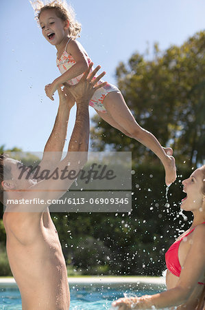 Family playing in swimming pool Stock Photo - Premium Royalty-Free, Image code: 6113-06909345